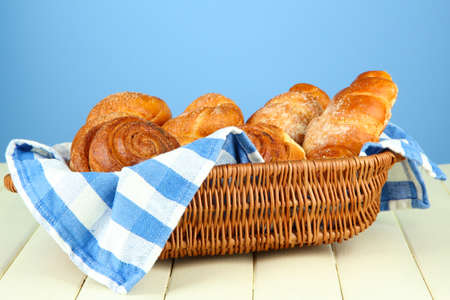 Composition with buns in wicker basket, on wooden table, on color background photo
