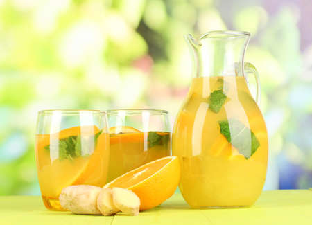 Orange lemonade in pitcher and glasses on wooden table on natural background Stock Photo - 20257799