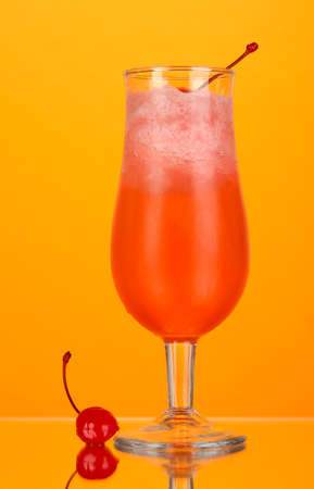Cherry cocktail with ice on orange background photo