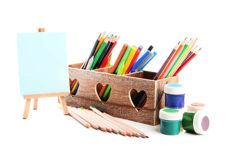 Different pencils in wooden crate, paints and easel, isolated on white photo