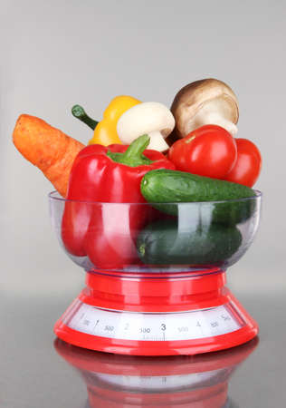 Fresh vegetables in scales on gray background photo