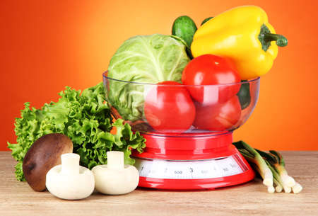 Fresh vegetables in scales on table on orange background photo