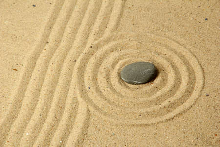 Zen garden with raked sand and round stone close up Stock Photo - 20257612