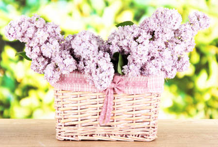 Beautiful lilac flowers on table on bright background photo