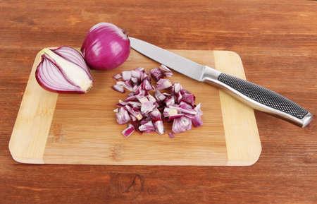 Cutting purple onion on wooden background photo