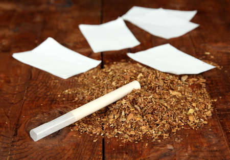 rolling paper: Tobacco and rolling paper, on wooden background Stock Photo