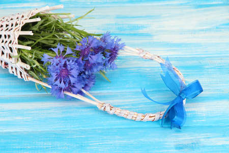 Beautiful bouquet of cornflowers in basket on blue background photo