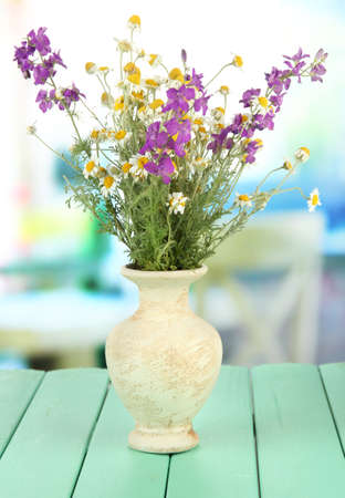 Bouquet of wild flowers in vase, on bright background photo