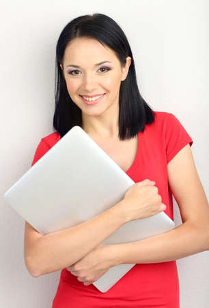 Beautiful young woman with notebook in room photo