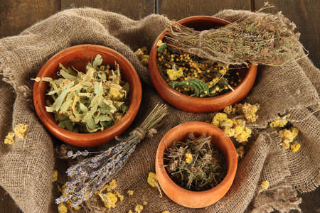 bagging: Medicinal Herbs in wooden bowls on bagging close-up