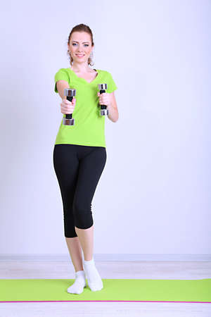 Beautiful young woman exercises with dumbbell photo