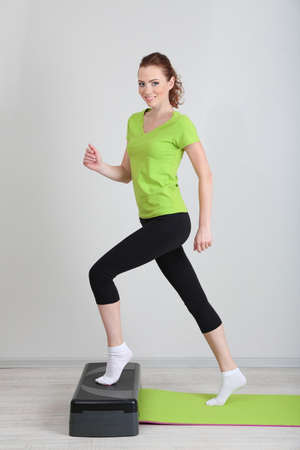 aerobic exercise: Beautiful young woman exercises on stepper Stock Photo