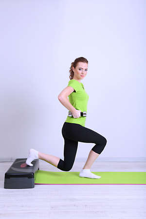 Beautiful young woman exercises with dumbbell on stepper photo
