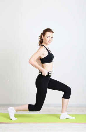 aerobic exercise: Beautiful young woman exercises with dumbbell