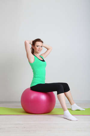 Portrait of beautiful young woman exercises with gym ball photo