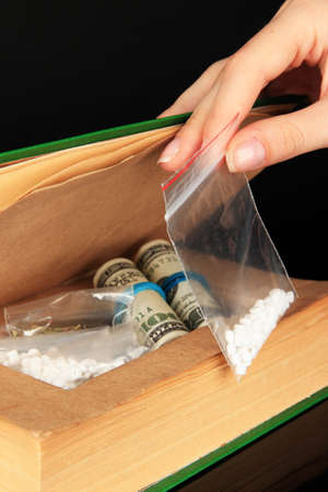 narcotics: Hand holding narcotics near book-hiding place isolated on black Stock Photo