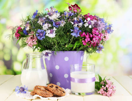 Beautiful bouquet in pail on wooden table on natural background photo