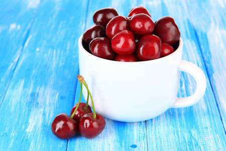 Cherry berries in cup on wooden table close-up photo