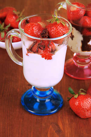 Delicious strawberry desserts in glass vase on wooden table close-up photo
