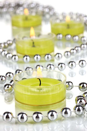 Lighted candles with beads close up photo