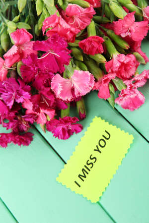 Bouquet of carnations, on color wooden background photo