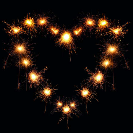 heart-shaped sparklers on black background photo