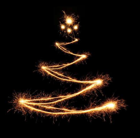 Christmas tree-shaped sparklers on black background photo