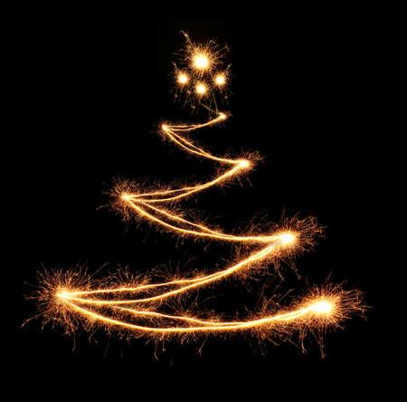 Christmas tree-shaped sparklers on black background