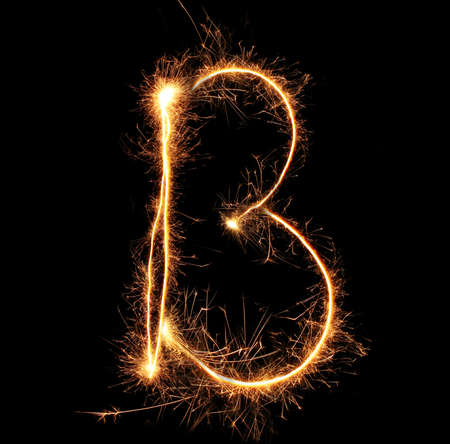 Letter B sparklers on black background photo