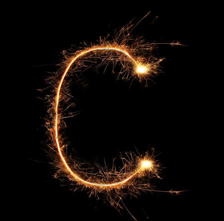 Letter C sparklers on black background photo