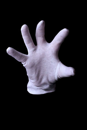 Hand in white glove making sign isolated on black photo