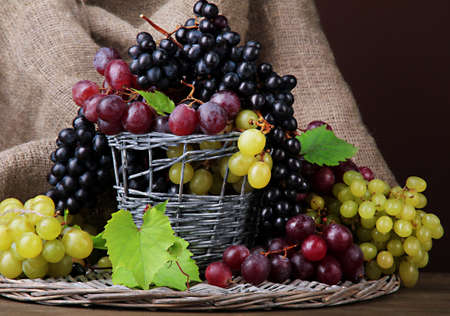 assortment of ripe sweet grapes in basket, on brown background photo