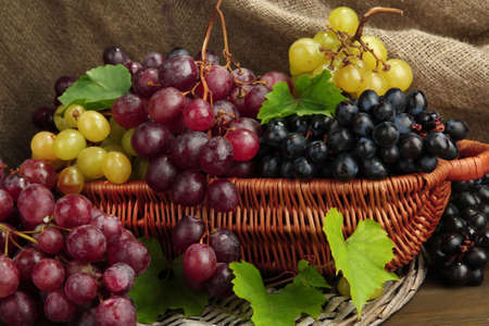 assortment of ripe sweet grapes in basket, on burlap background photo