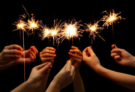 sparklers: beautiful sparklers in hands on black background  Stock Photo