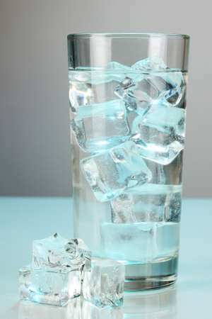 refrigerate: Ice cubes in glass on light blue background Stock Photo