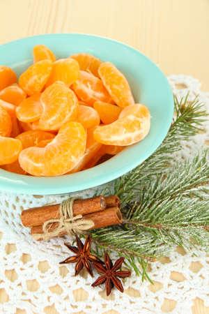 Tasty mandarines slices on color plate on light background photo