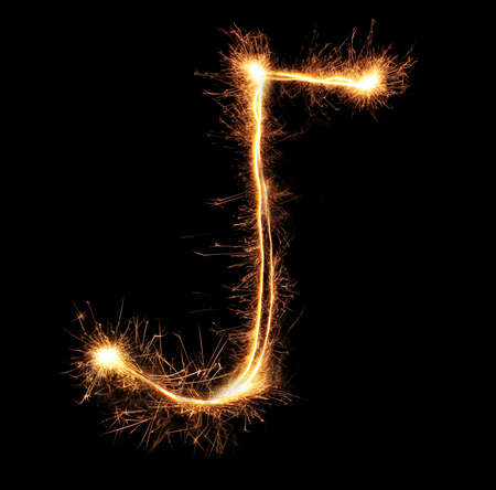 Letter J sparklers on black background photo