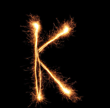 Letter K sparklers on black background photo