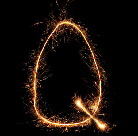 Letter Q sparklers on black background photo