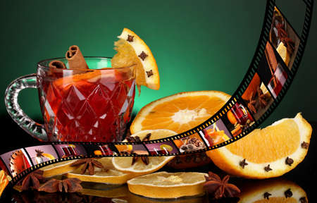 punch spice: Mulled wine in glass with photographic film of drinks on green background