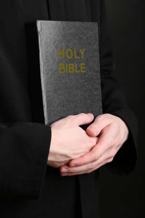 bible reading: Priest holding holy bible, close up