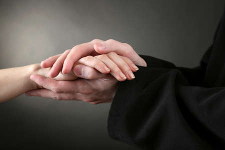 Priest holding woman hand, on black background photo