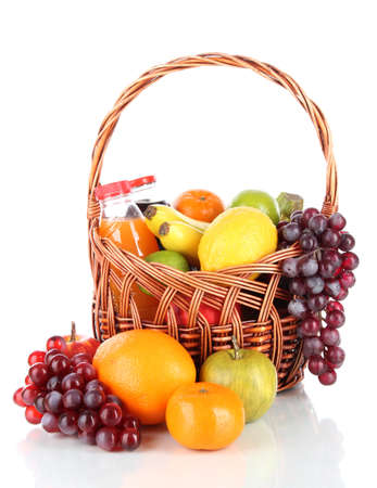 Different fruits in wicker basket with juice isolated on white photo