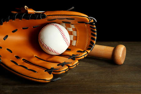 Baseball glove, bat and ball on dark background photo