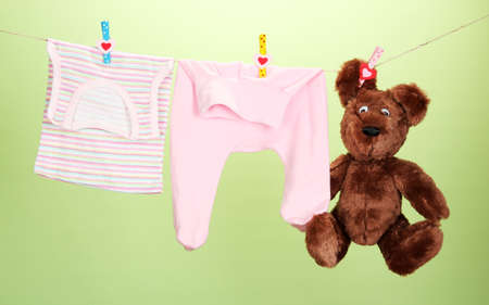 Baby clothes hanging on clothesline, on color background photo