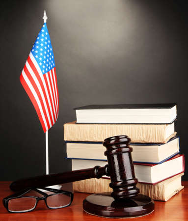 Wooden gavel, books and American flag on grey background photo