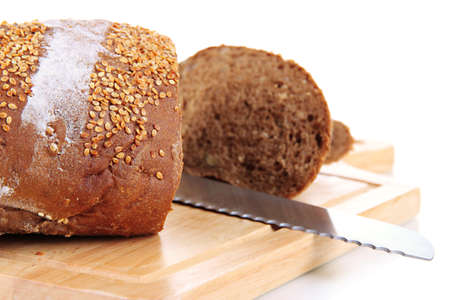 Bread with sesame seeds and knife on wooden board close up Stock Photo - 20700614