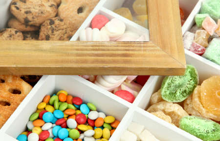 Multicolor candies and cookies in white wooden box close up photo