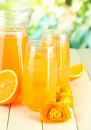 Glasses and pitcher of orange juice on wooden table, on green background photo