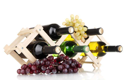 Bottles of wine placed on wooden stand isolated on white photo